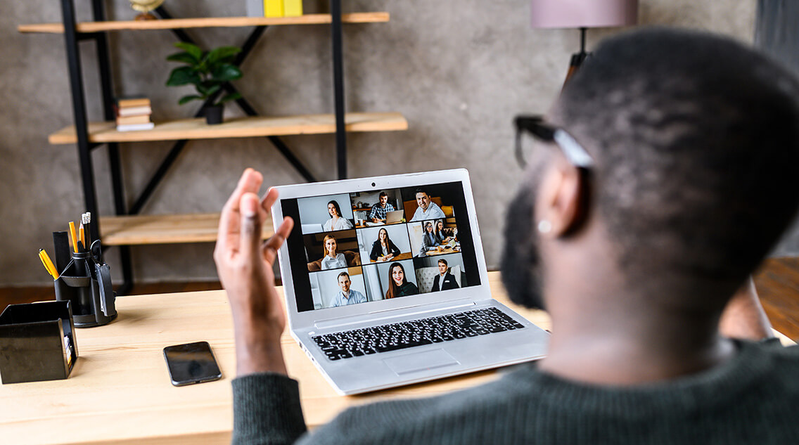 A male worker talking online with coworkers, back view of guy speaks and gestures to many people on video screen. Remote work, virtual meeting