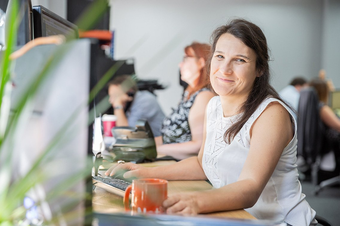 Solutions co-ordinator smiling while workking at her desk