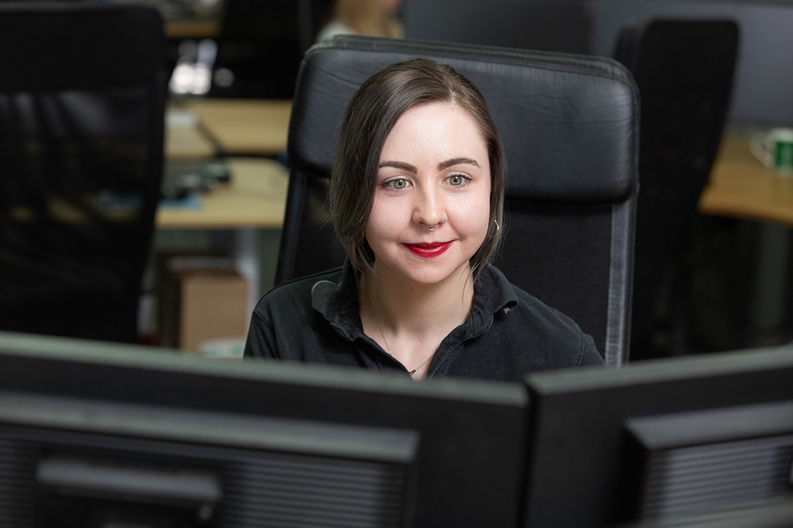 Customer Service Manager working at her desk, looking at the screens