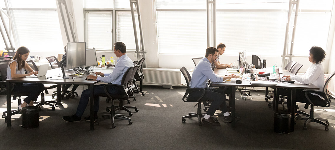 Diverse employees focused on working on desktops in shared office