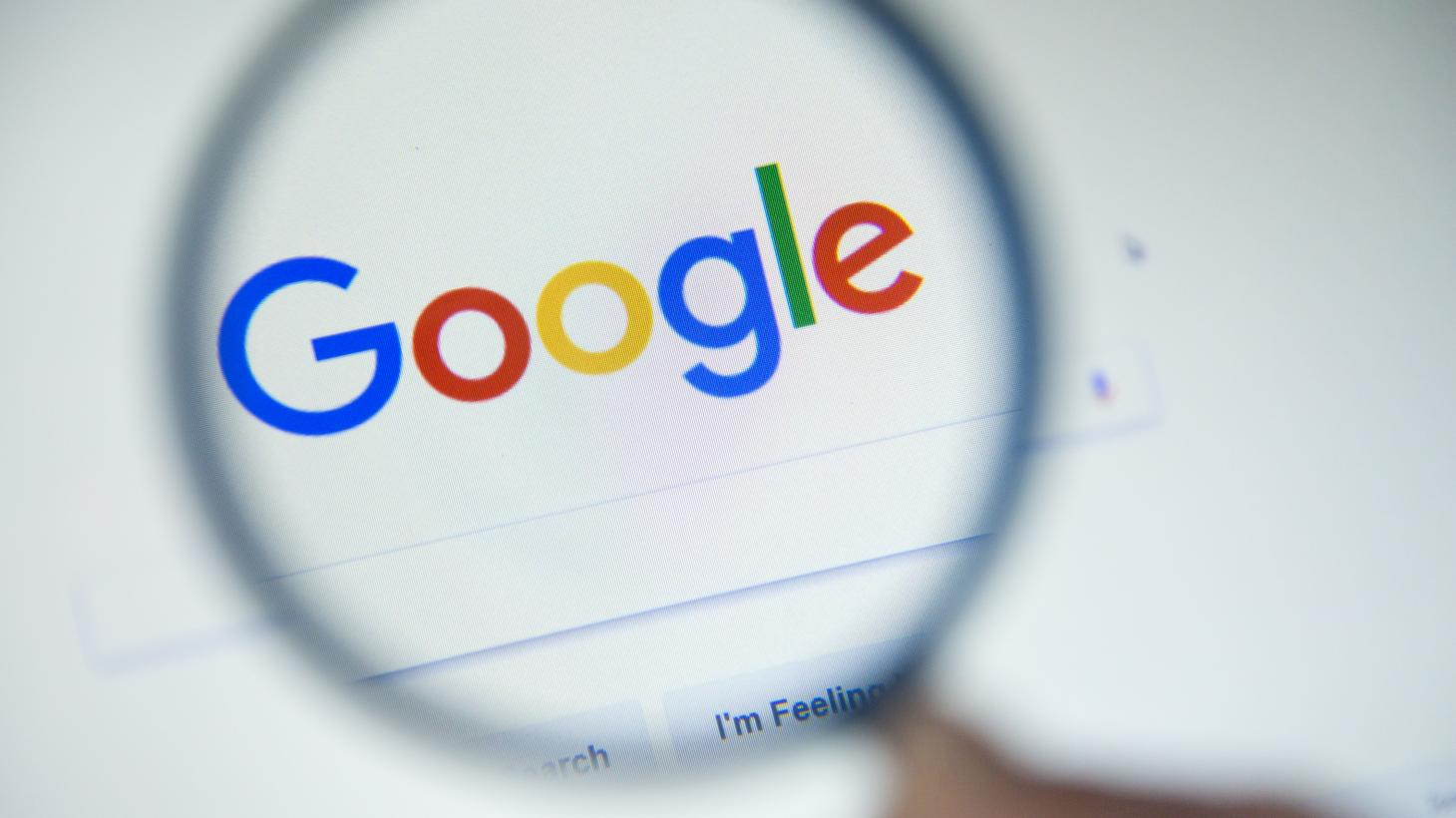 Google.fr homepage on the screen under a magnifying glass. Google is world's most popular search engine