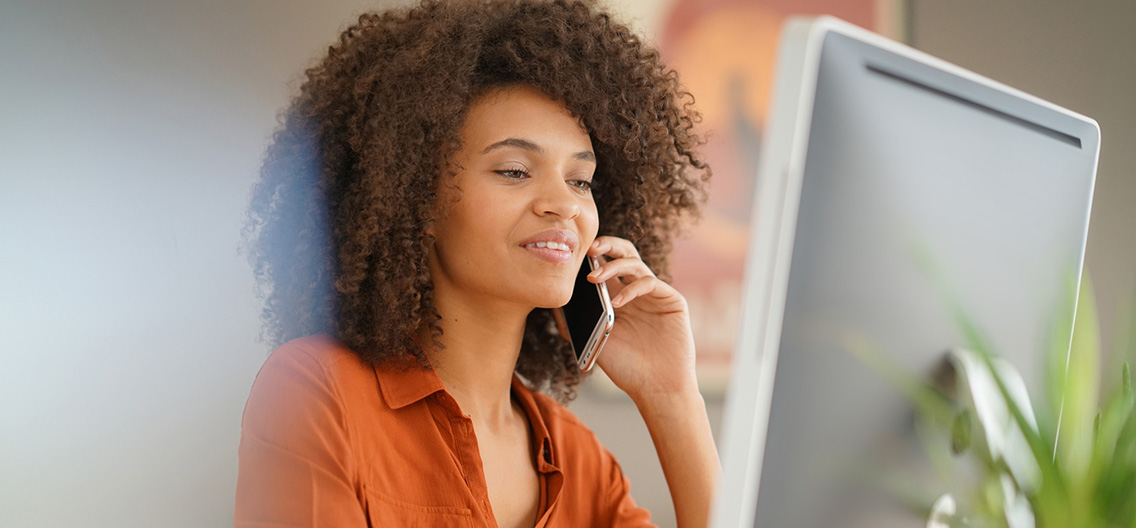 Business woman talking on the phone while looking at her computer screen