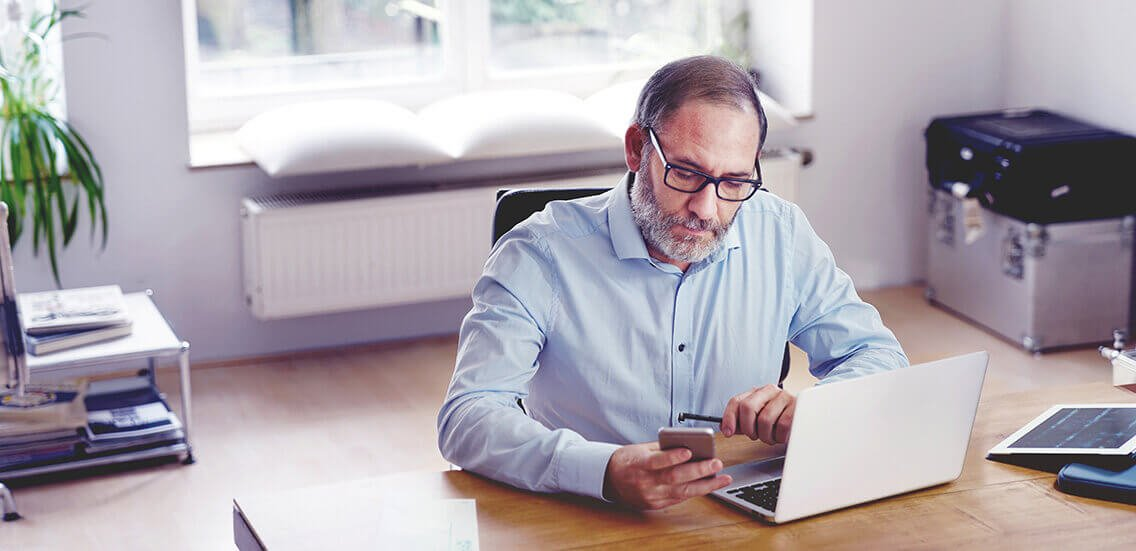 Grey Bearded mature man creative director sitting in modern office working with laptop computer on wooden desk. stylish design interior