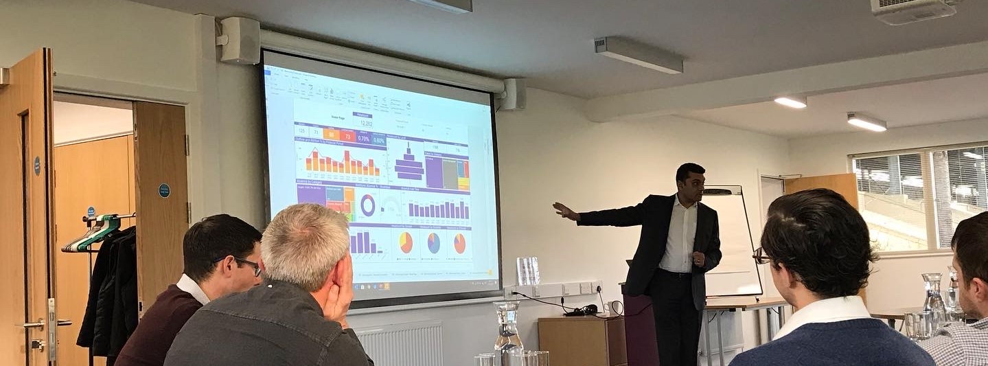 Man presenting a data dashboard in front of a crowded room