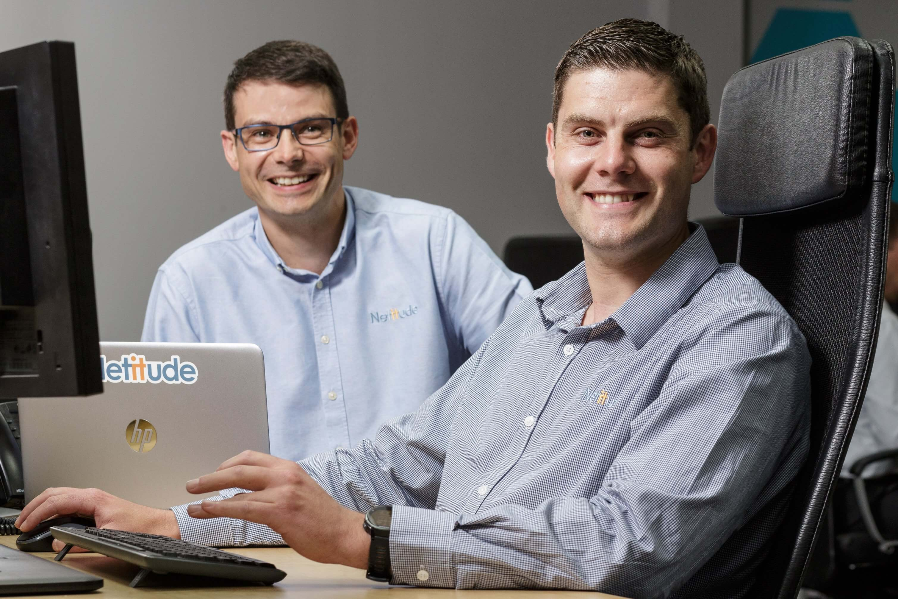 Service Delivery Director and Virtual IT Director working at a computer together, smiling at the camera