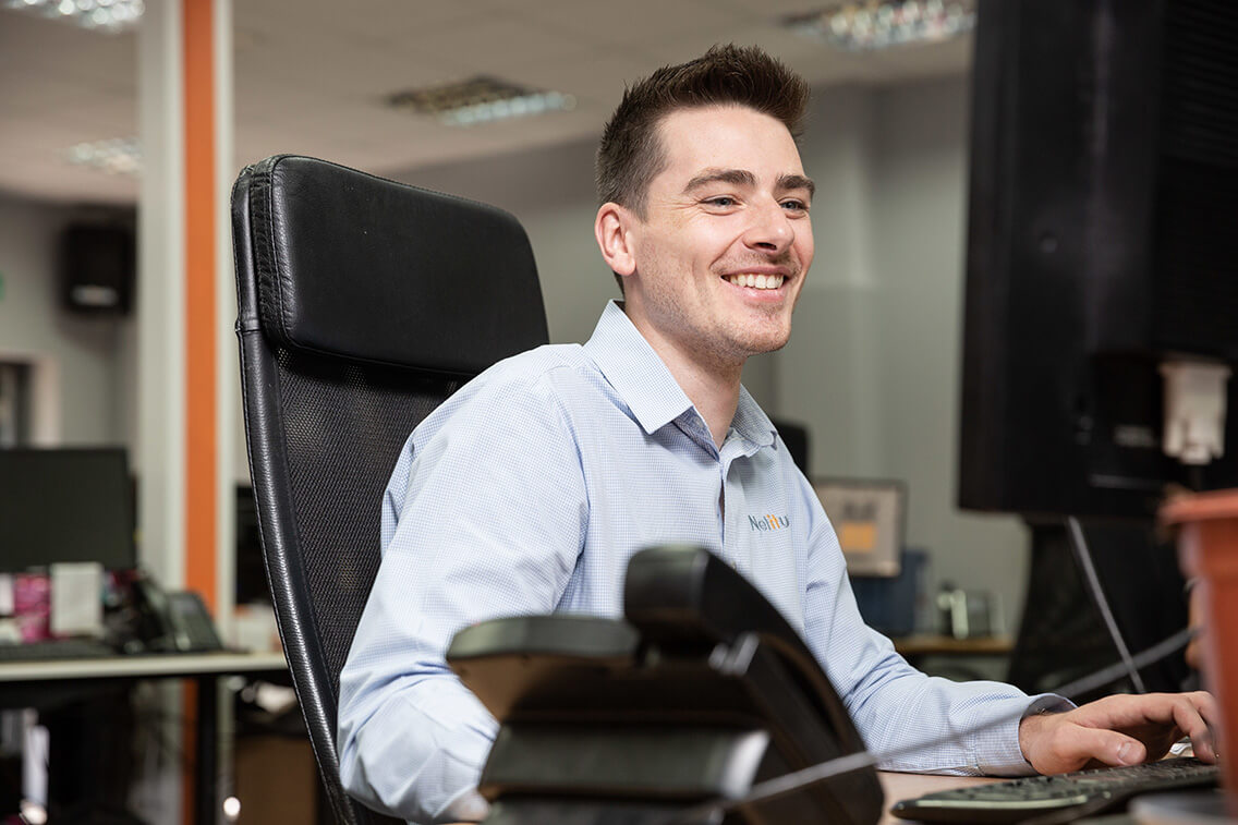 Technical Alignment Engineer, smiling while working at his computer