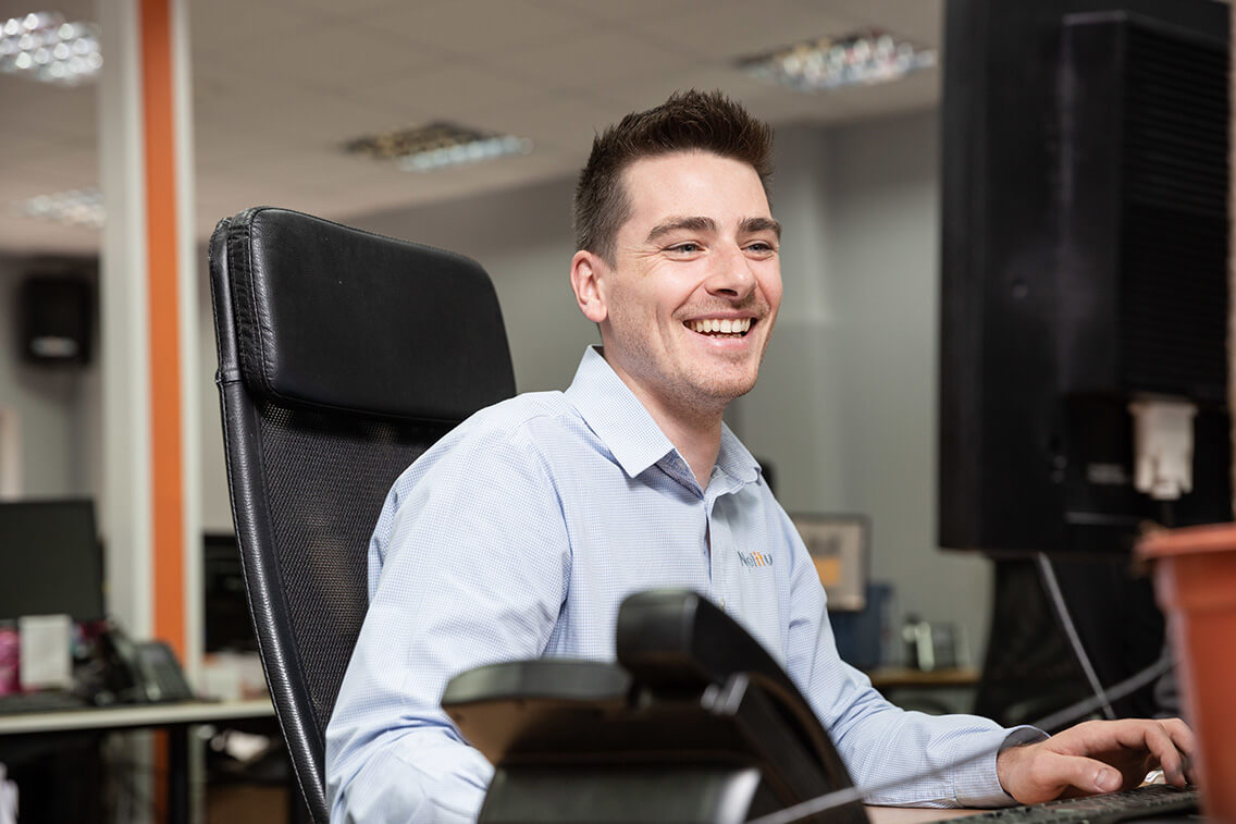 Young male engineer laughing while working at his computer