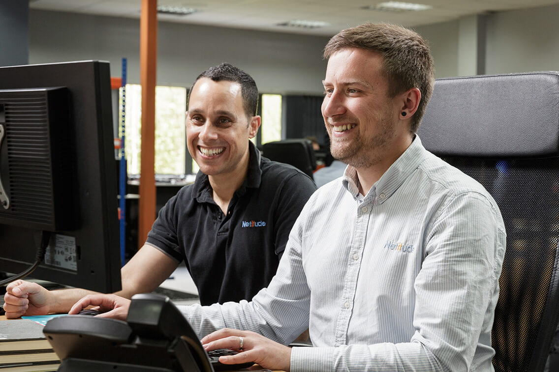 Operations Centre Manager and Technical Alignment Manager working at a computer together