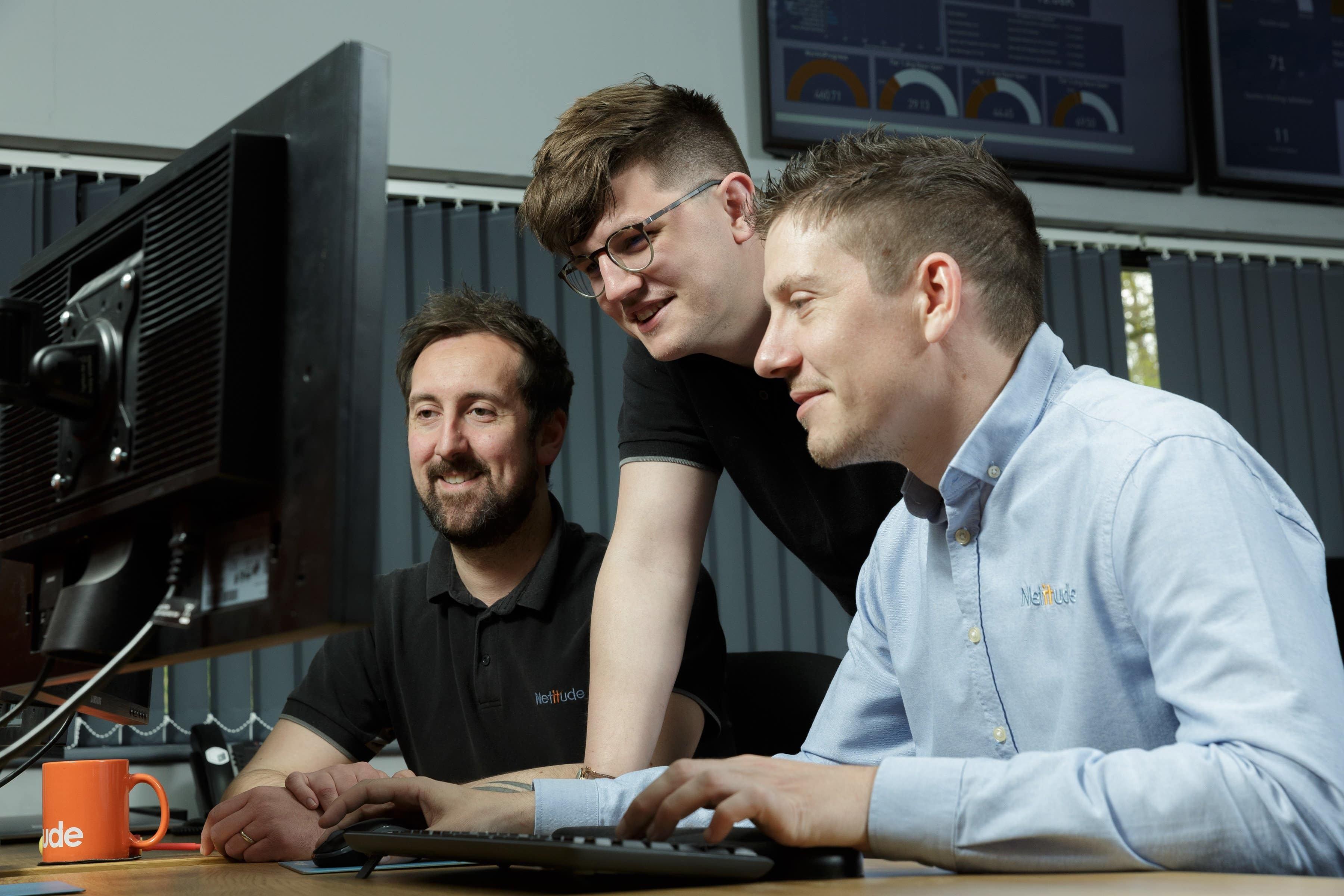 Three male project engineers working at a computer together